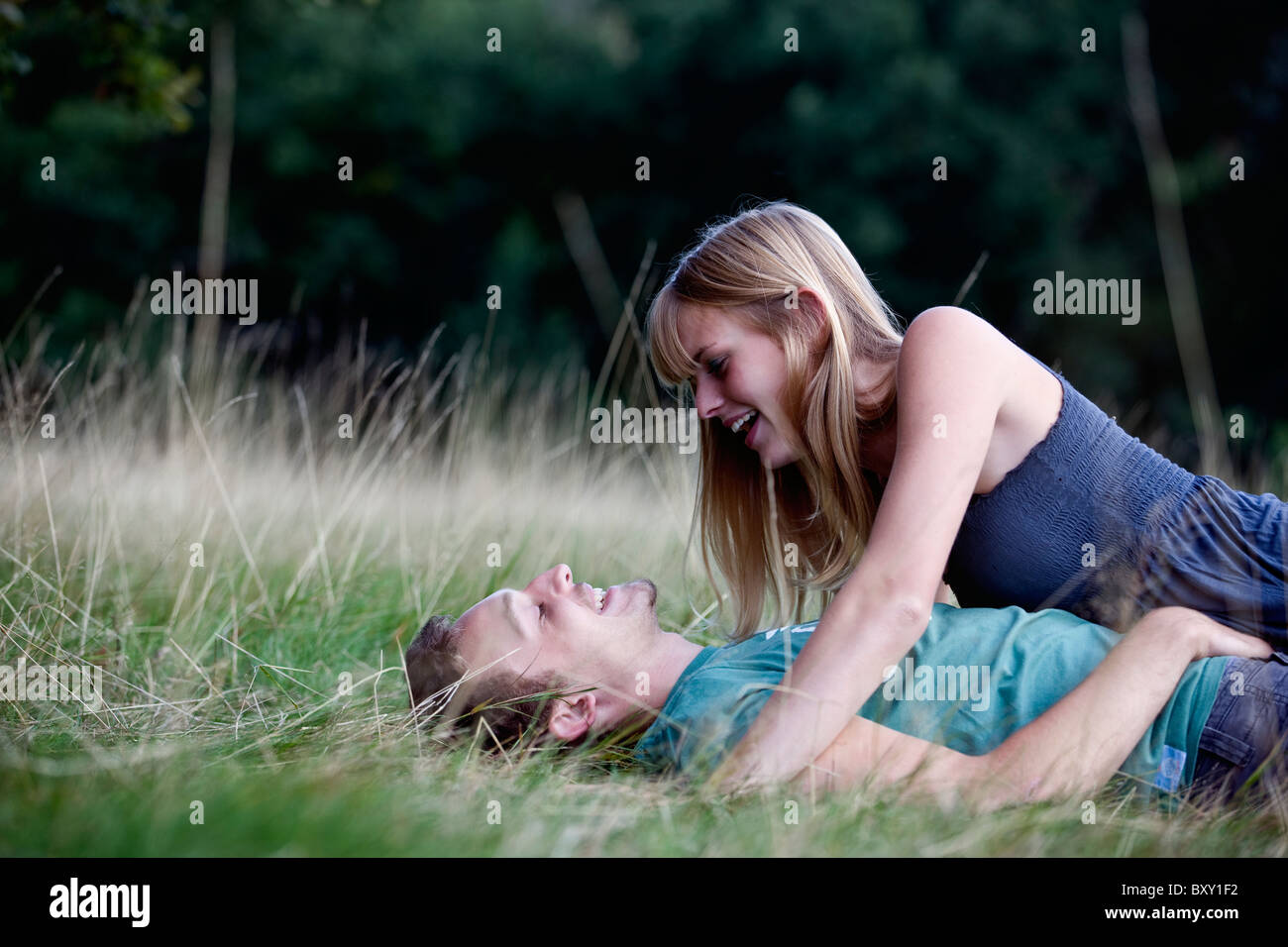 A young couple lying on the grass, laughing - Stock Image