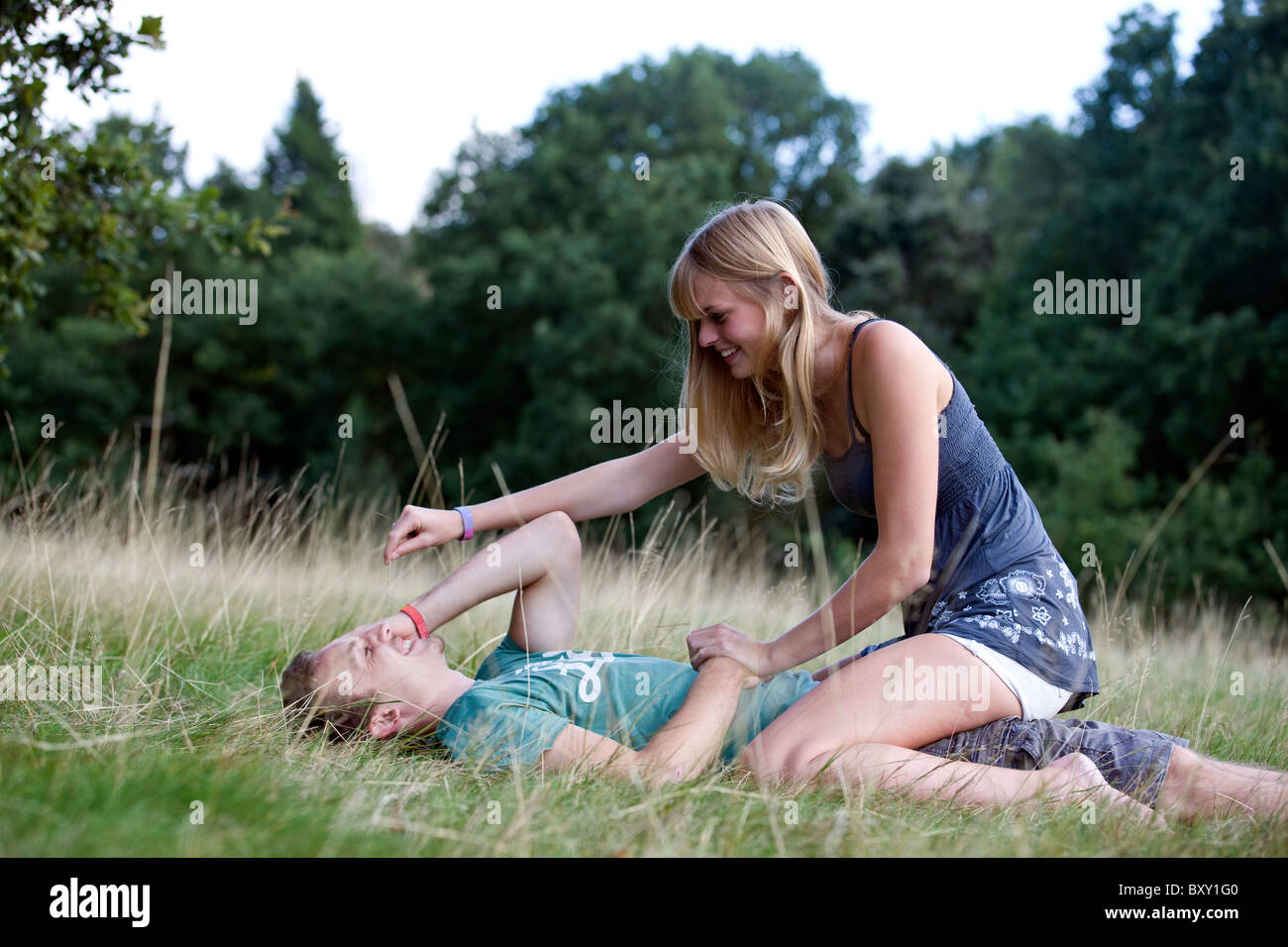A young couple on the grass, laughing - Stock Image