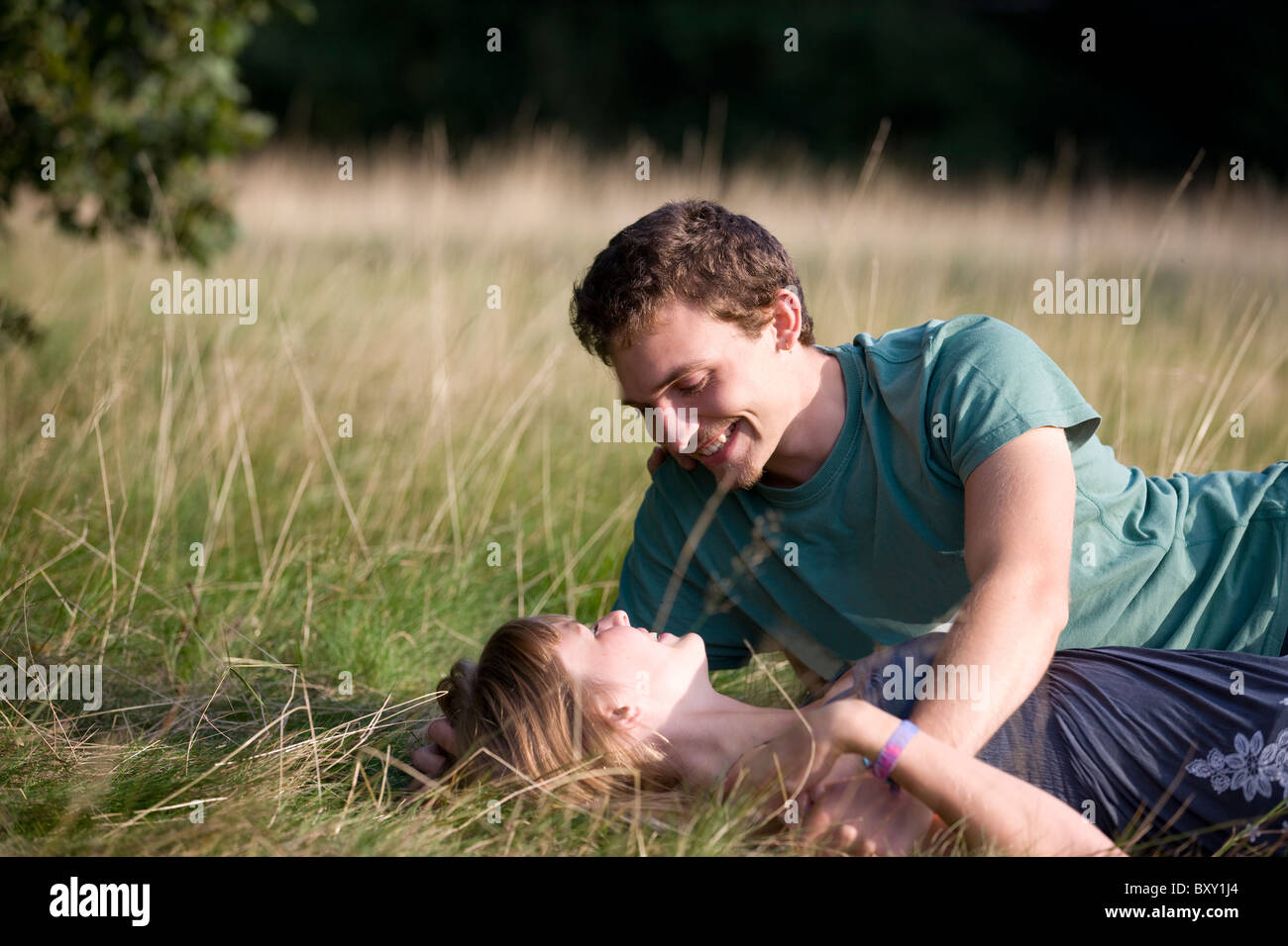 A romantic young couple lying on the grass - Stock Image