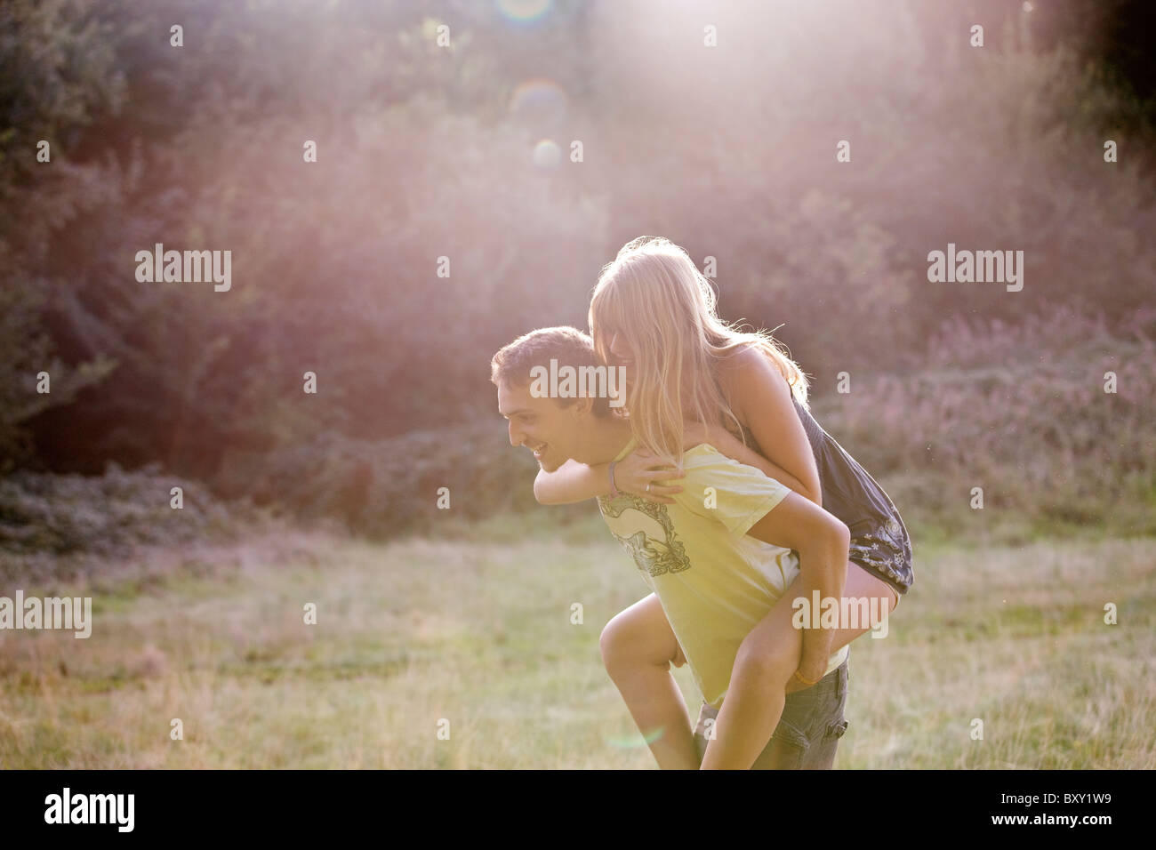A young couple outdoors, man giving the woman a piggyback - Stock Image