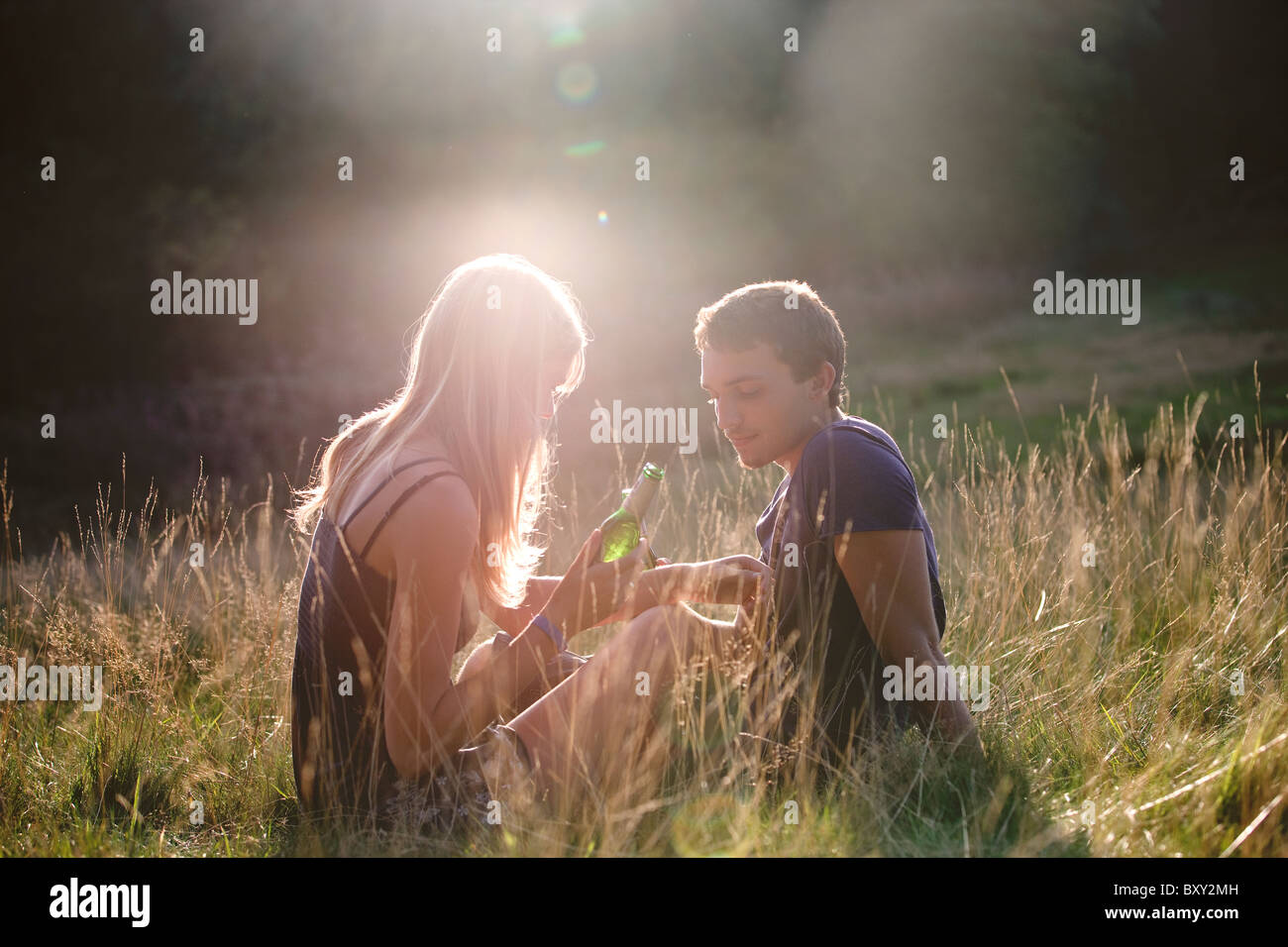 A young couple sitting outdoors in the evening sun, drinking beer - Stock Image