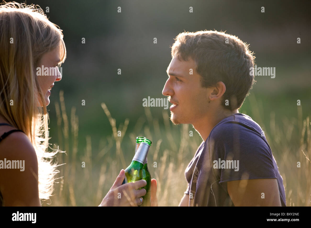 A young couple sitting outdoors, drinking beer - Stock Image