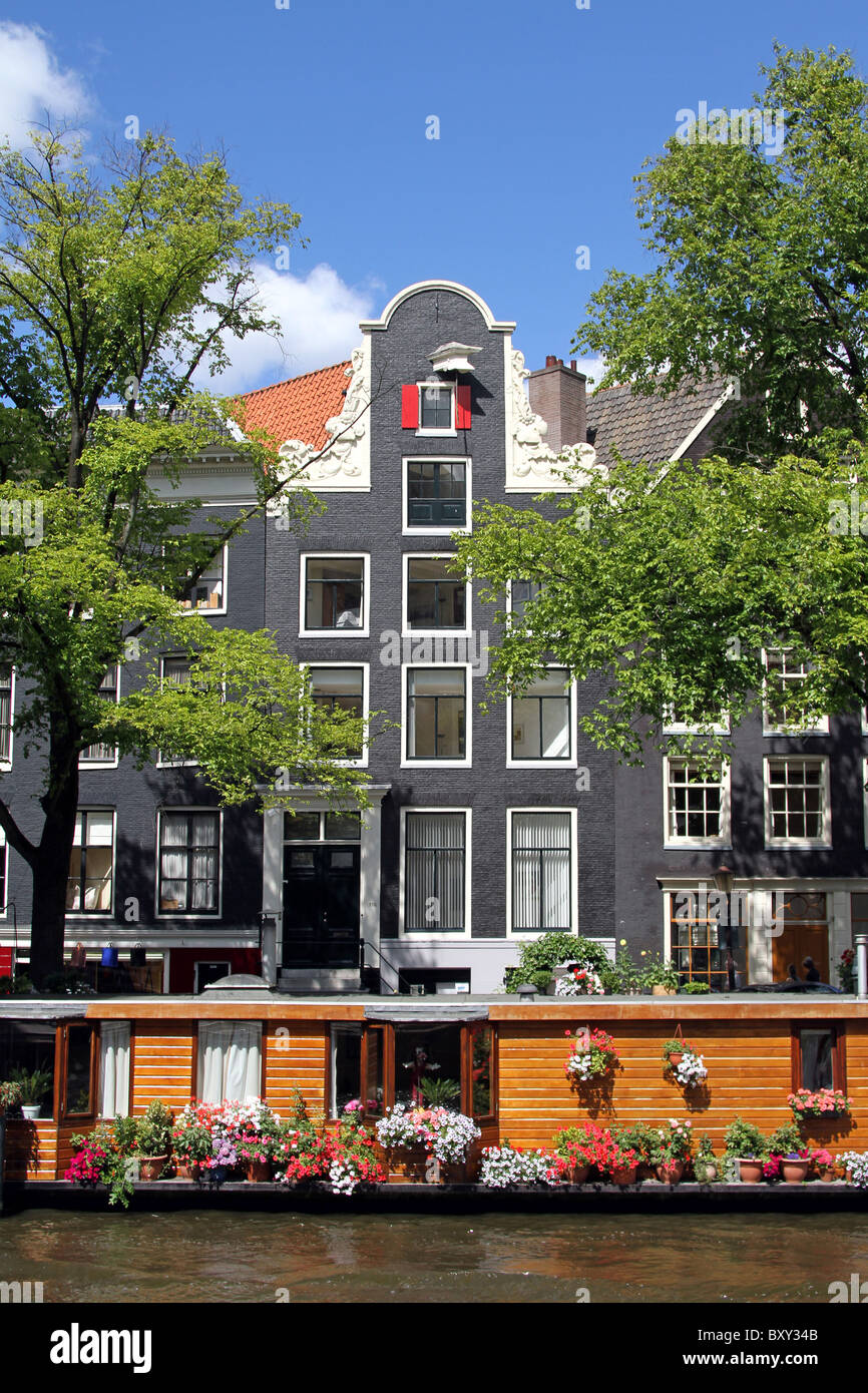 Traditional Dutch house and house boat on Prinsengracht in Amsterdam, Holland - Stock Image