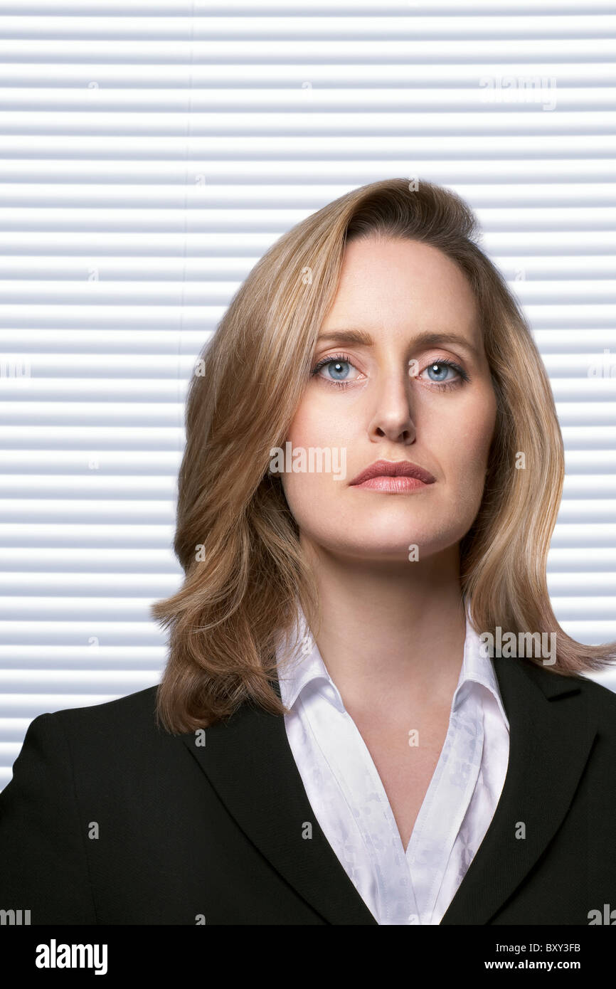 Portrait of female detective with serious facial expression infront of white slatted blinds - Stock Image