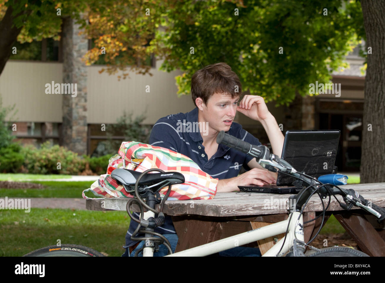 A young male student shows dismay at what he sees on his computer screen - Stock Image