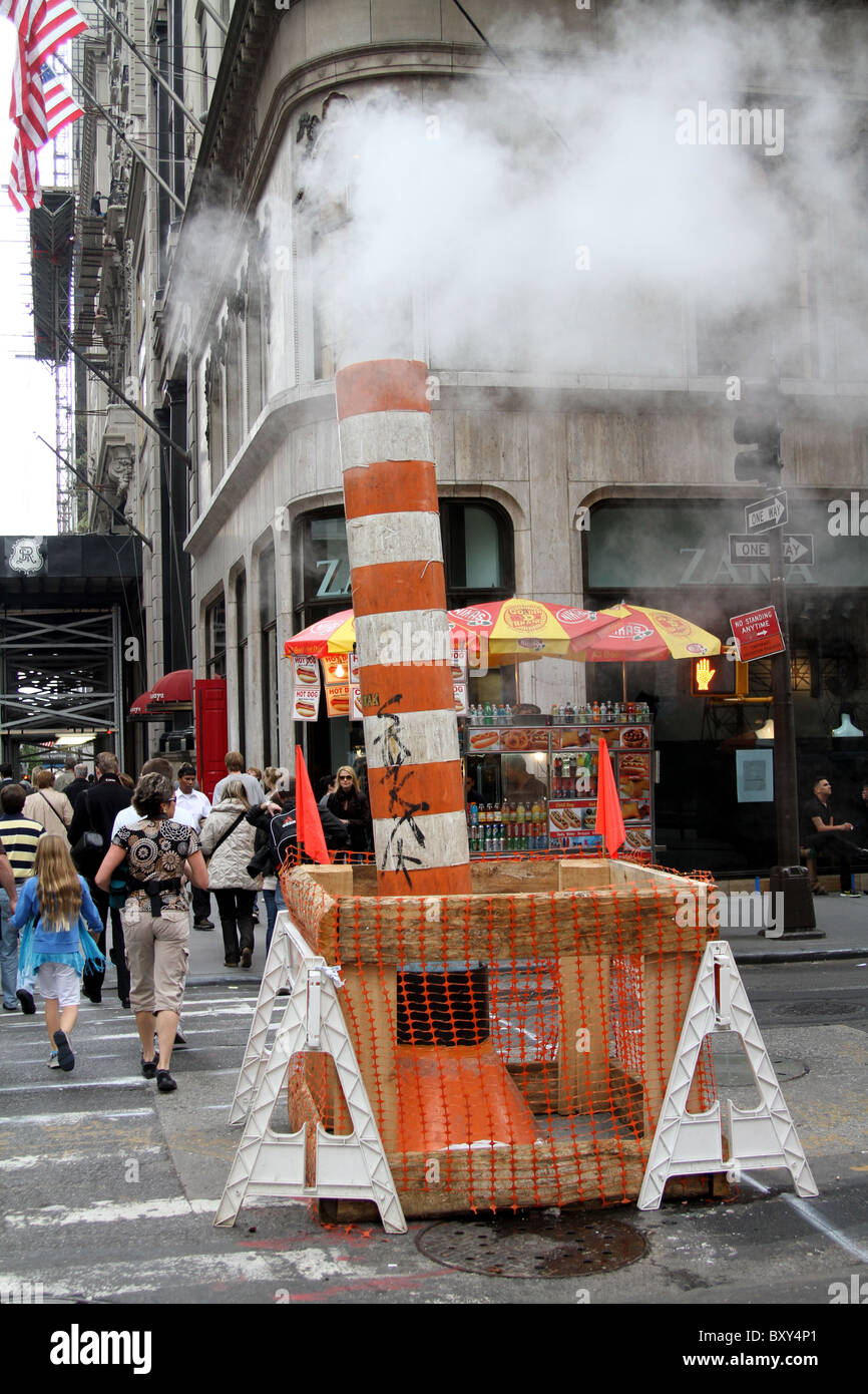 Striped steam vent from the Con Edison steam system in roadworks in New York, America - Stock Image