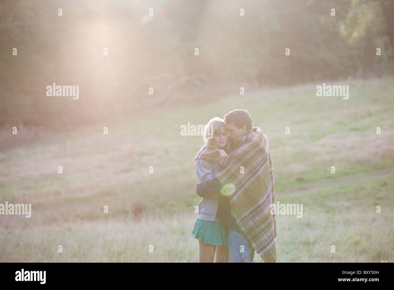 A young couple embracing outdoors, wrapped in a blanket - Stock Image