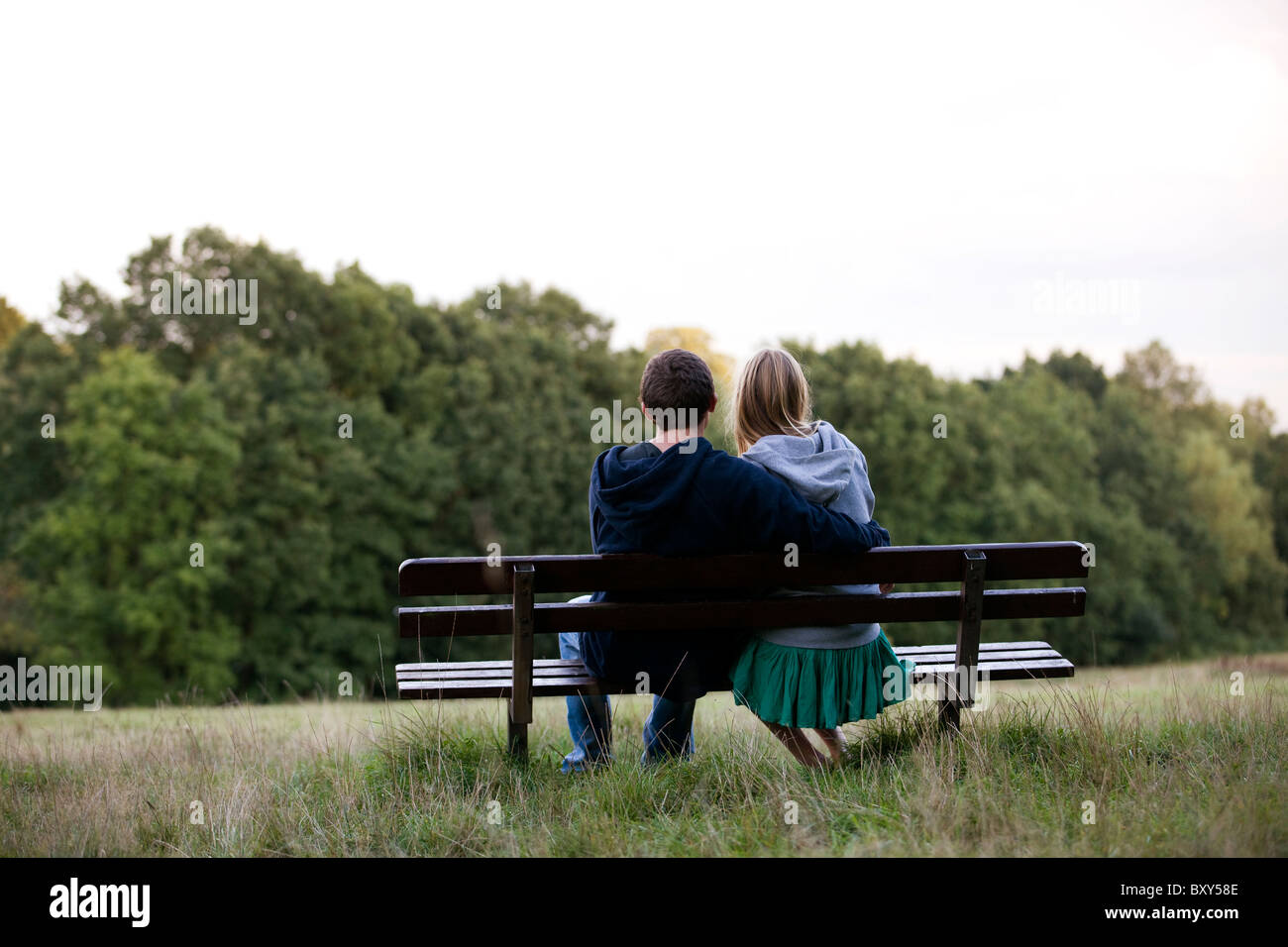 Rear view of young couple on a park bench - Stock Image