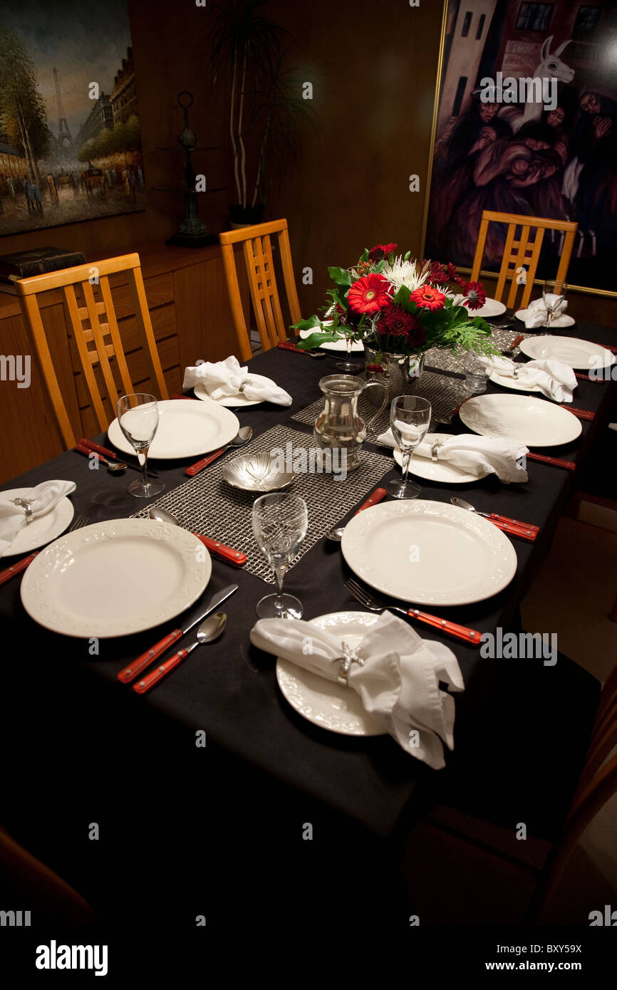 Table setting on a black tablecloth with a floral arrangement and pictures on the wall of the dining room. & Table setting on a black tablecloth with a floral arrangement and ...