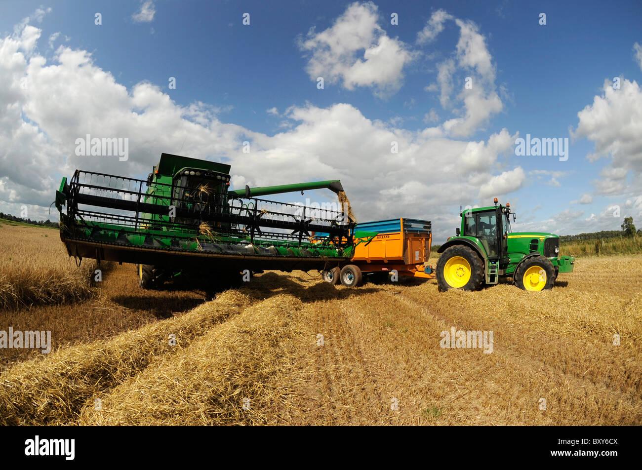 A John Deere Combine Harvester Harvesting Barley In Field At Holme Gate Farm Near Warwick On Eden