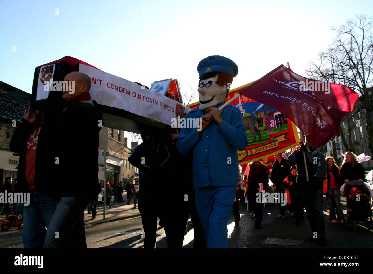 Coffin carried by protester and a protester dressed as Postman Pat at Witney england during the royal mail protest. - Stock Image
