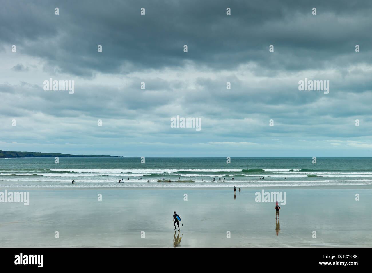 Waves, tide and surfers with surfboards at Lahinch - Lehinch - beach, County Clare, Ireland - Stock Image