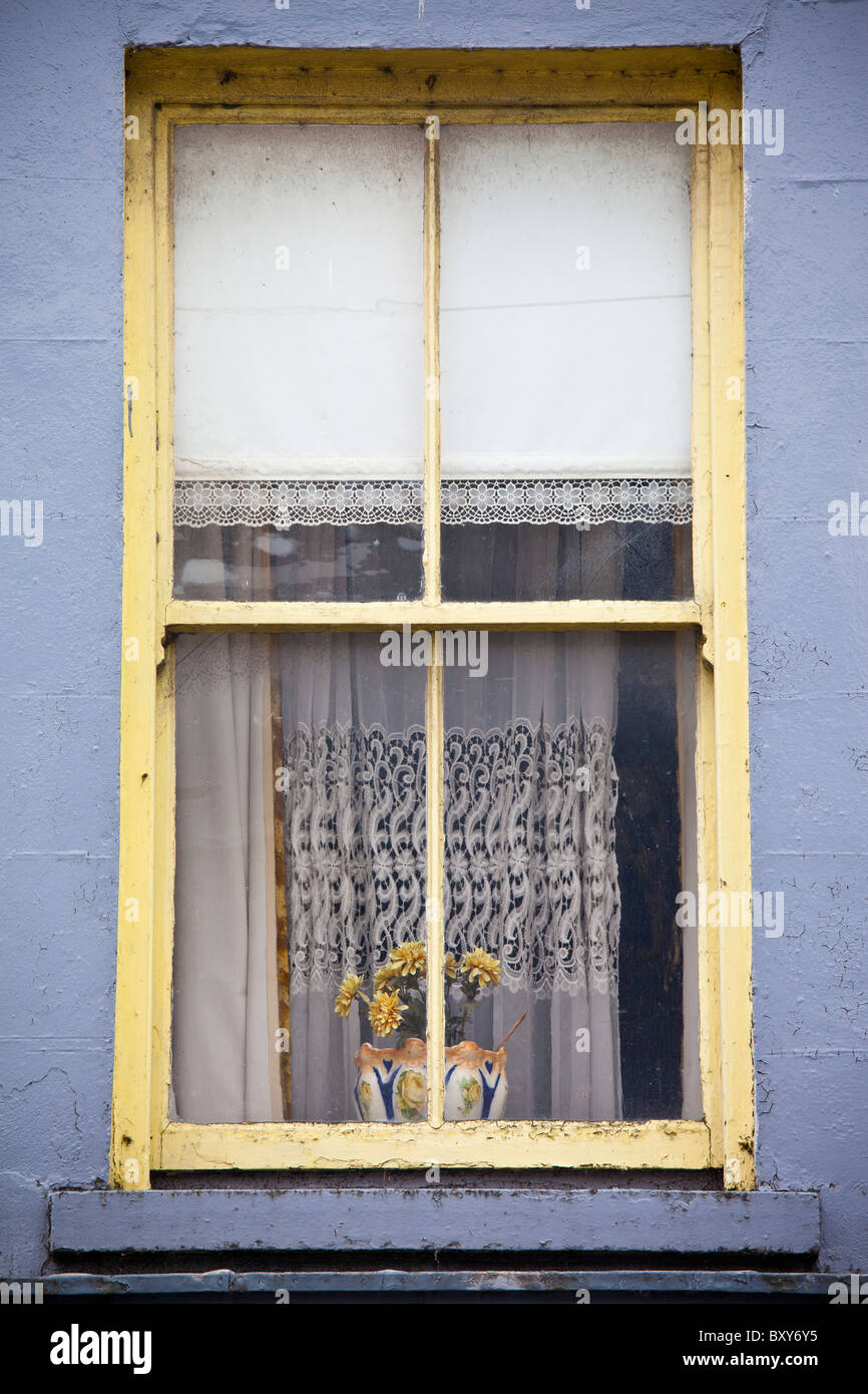 Lace curtains and a lace-trimmed roller blind in typical window in Ennistymon (Ennistimon), County Clare, West of - Stock Image