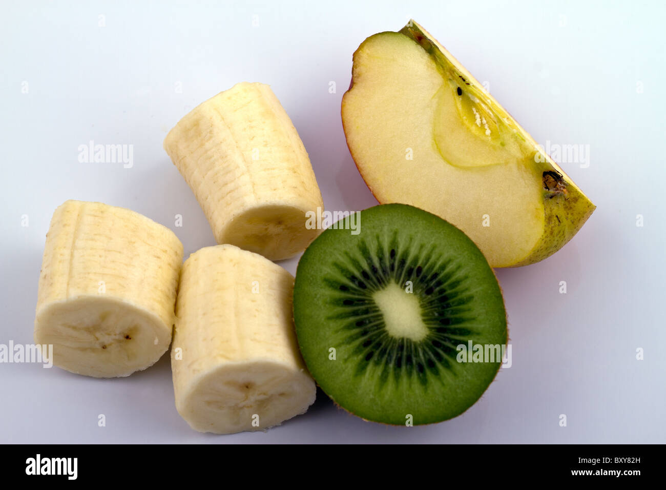 Banana Kiwi And Apple Pieces On Reflecting White Surface Stock