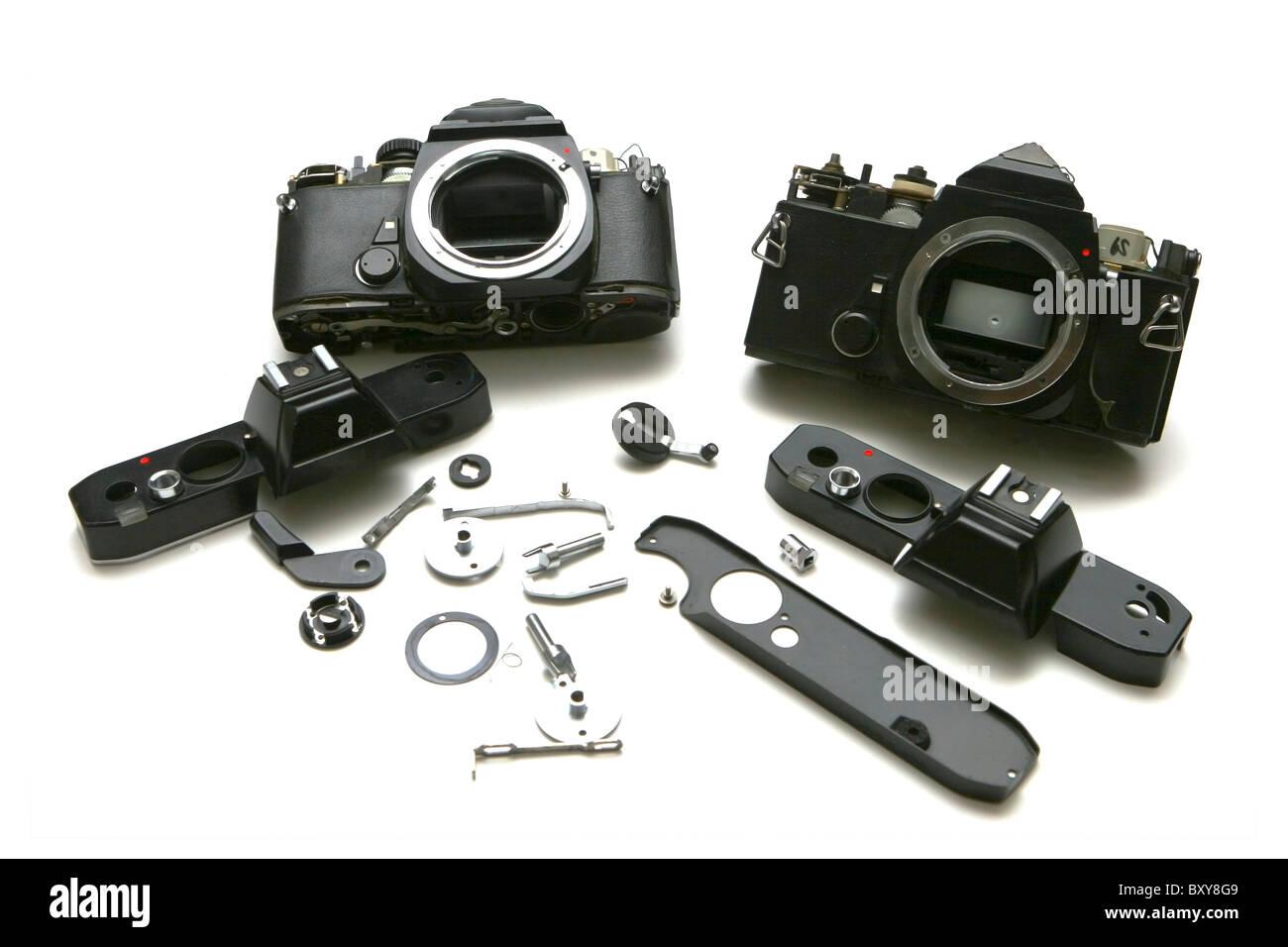 2 film SLR Cameras, disassembled for repair. On White. Branding removed. - Stock Image