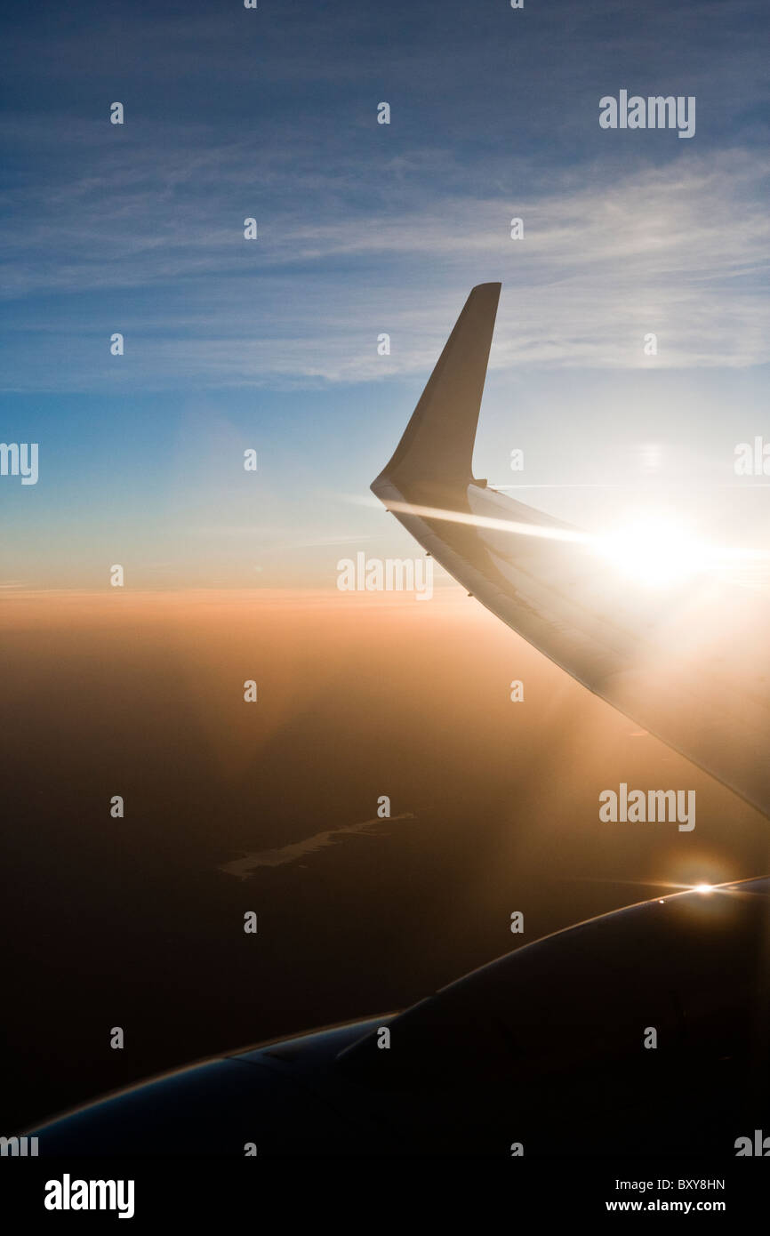 view of 737 wing, with winglets, traveling at dusk with sunset starburst - Stock Image