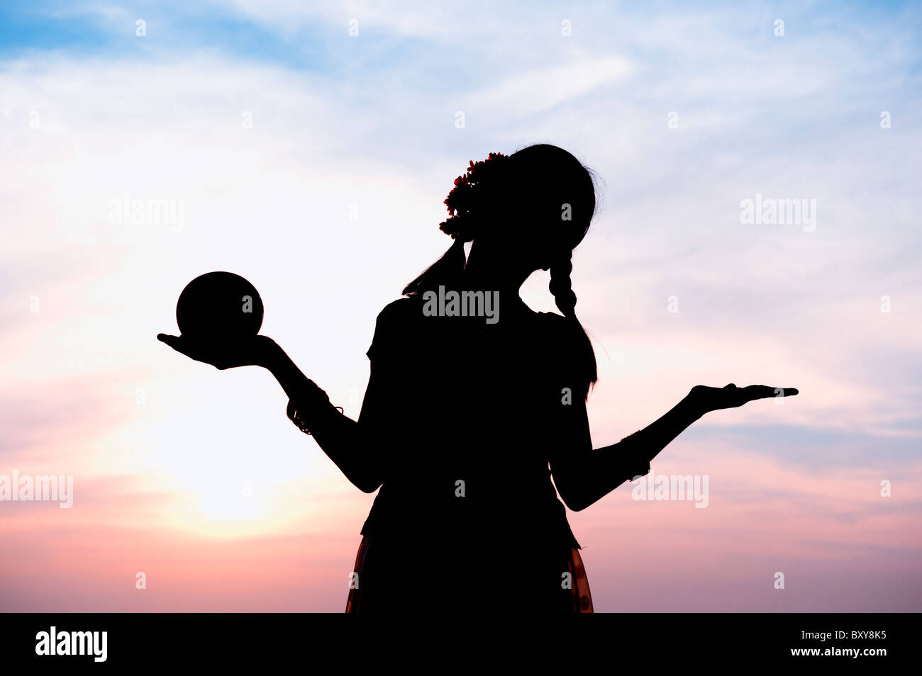 Indian girl silhouette balancing a round shape in her hand in an unconcerned carefree pose. India - Stock Image