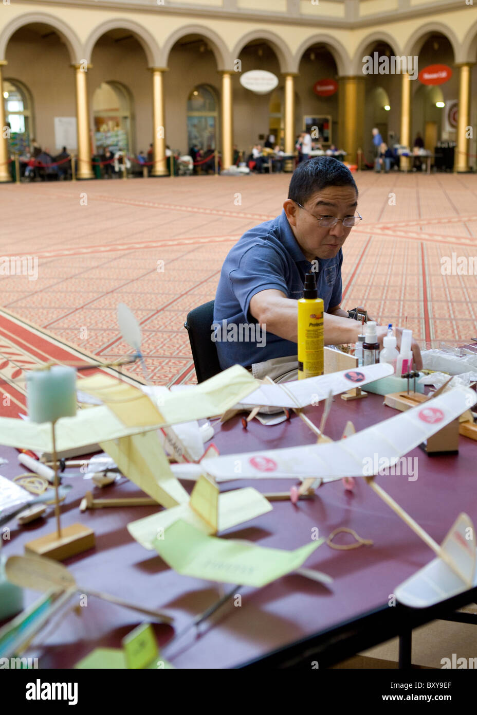 A middle aged Asian man constructing model airplanes - Stock Image