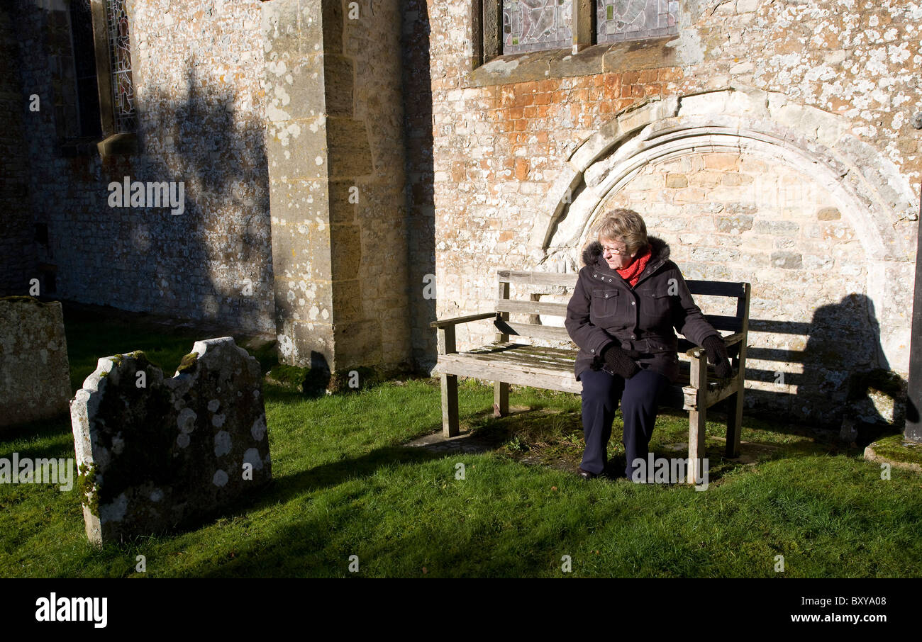 A lady sitting in a churchyard - Stock Image