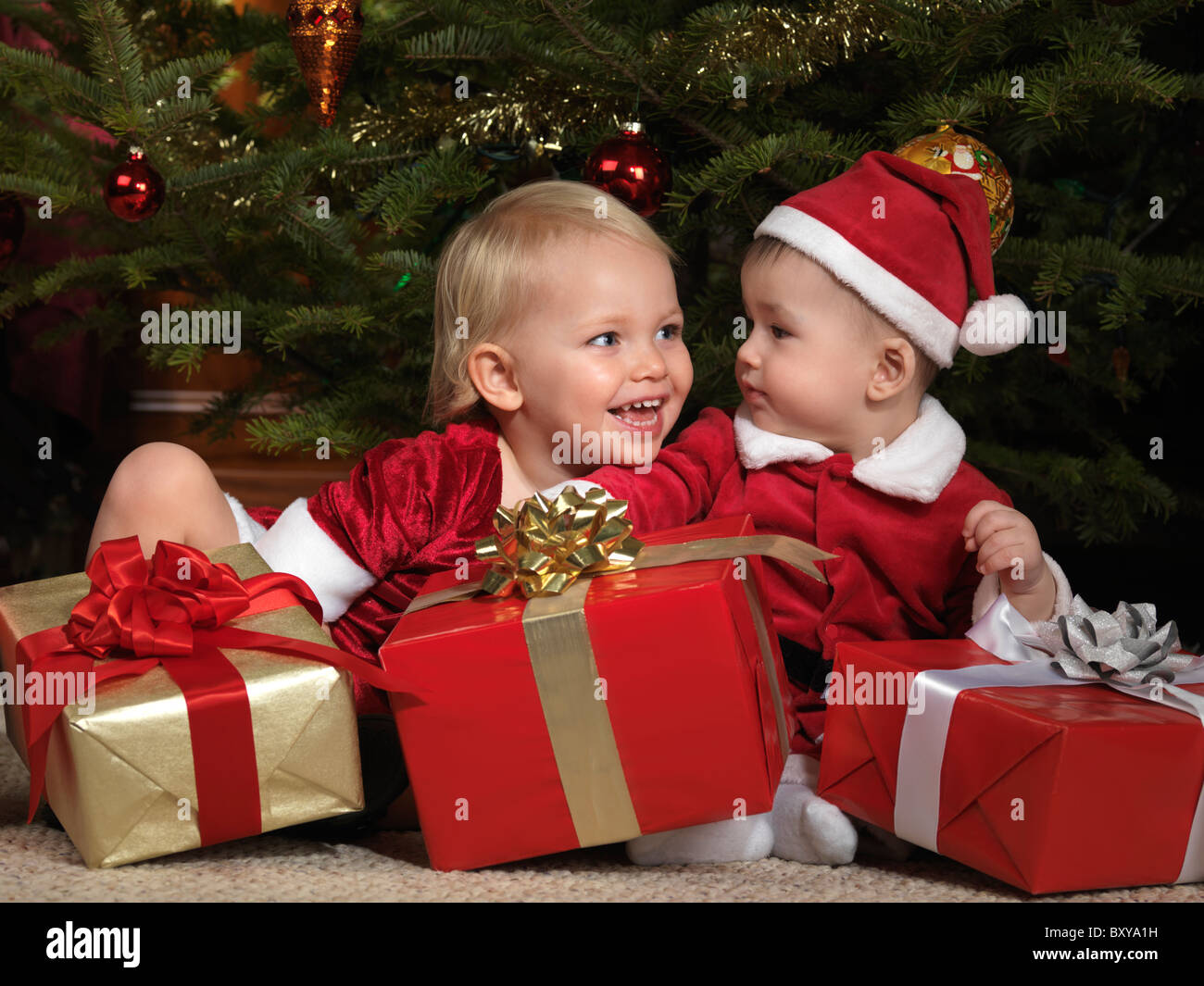 Two year old girl and an eight month old boy sharing gifts under a Christmas tree Stock Photo