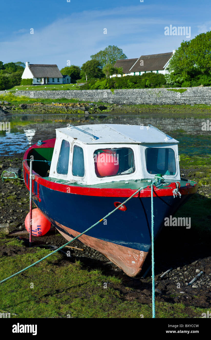 Brightly coloured fishing boat in the quay and thatched cottages at Ballyvaughan, County Clare, West of Ireland - Stock Image