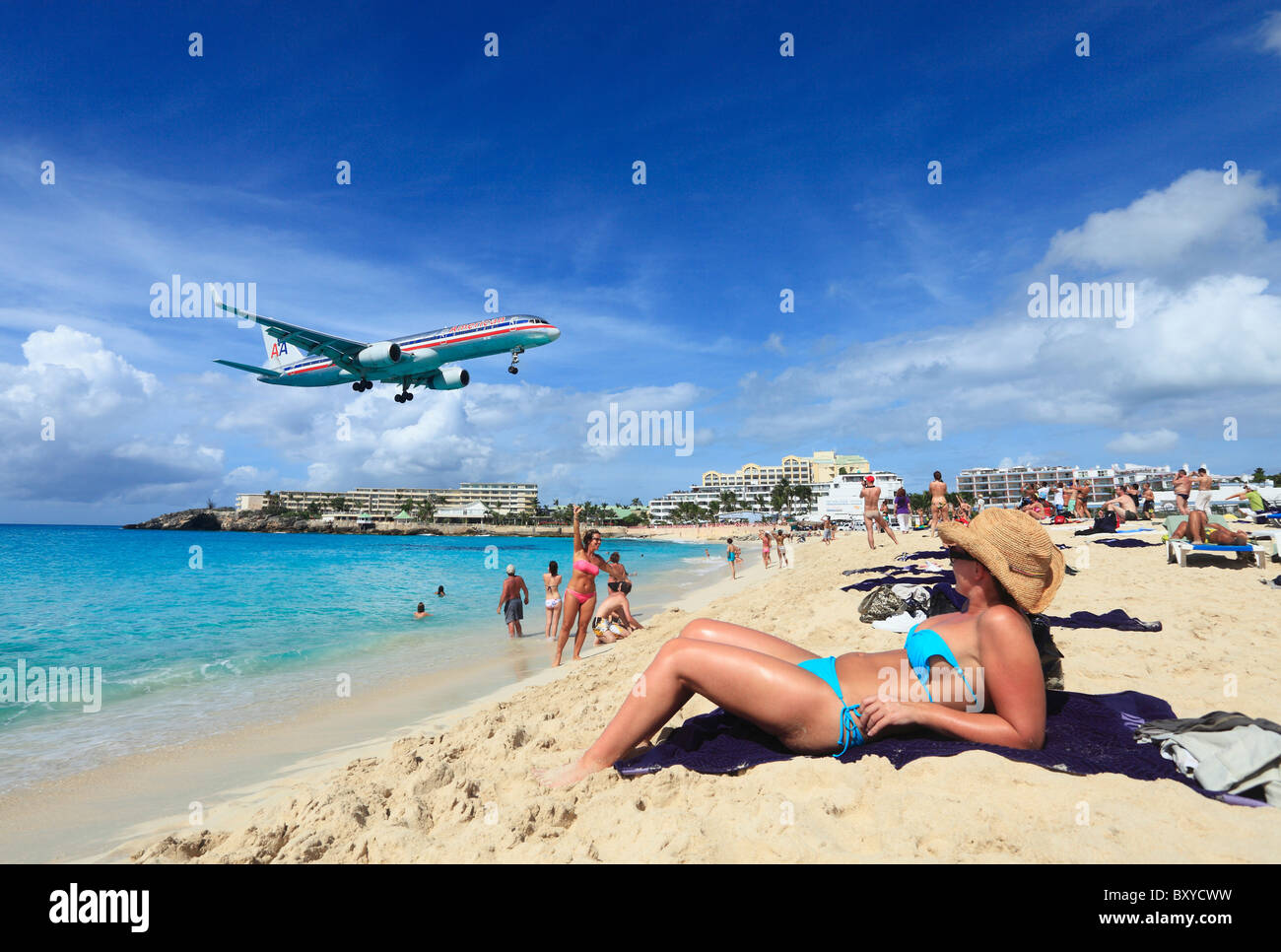 American Airlines Jet landing across the Maho beach at St.Maarten Princess Juliana Airport - Stock Image