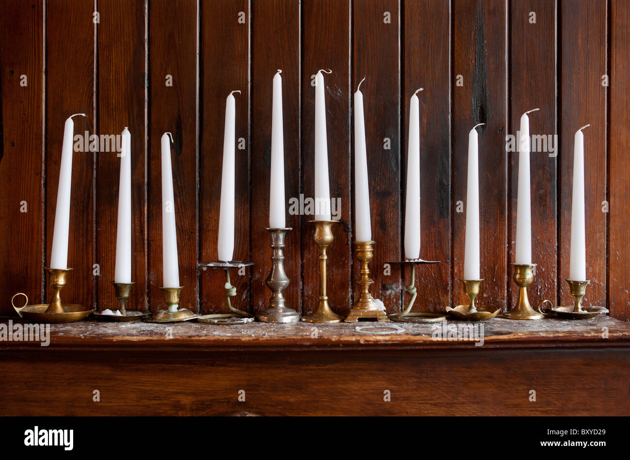 Row of Candles in candlestick holders above fireplace - Stock Image
