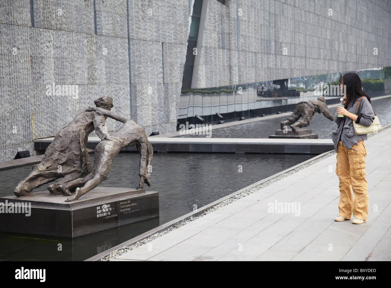 Woman looking at statues at Memorial to the Nanjing Massacre, Nanjing, Jiangsu, China - Stock Image