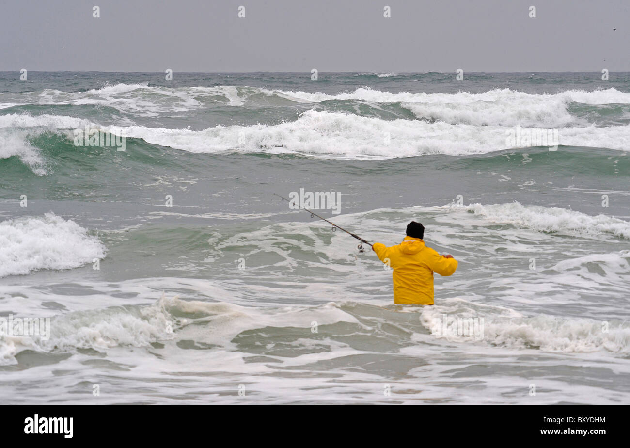 Man surf fishing in cold northwest water, Cannon Beach, Oregon, USA - Stock Image