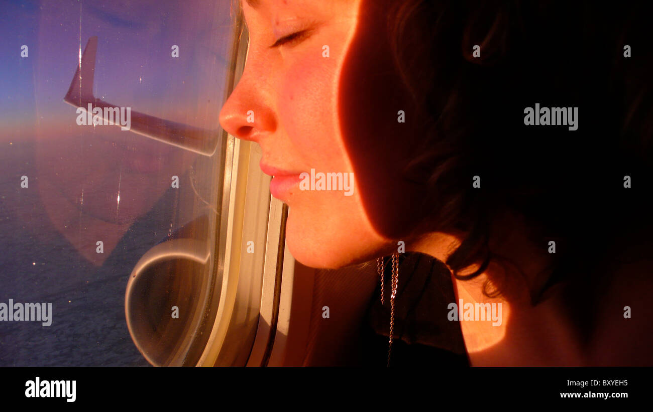 blonde woman looks out of an airplane window in flight and has her face lit up pink by the sunrise - Stock Image