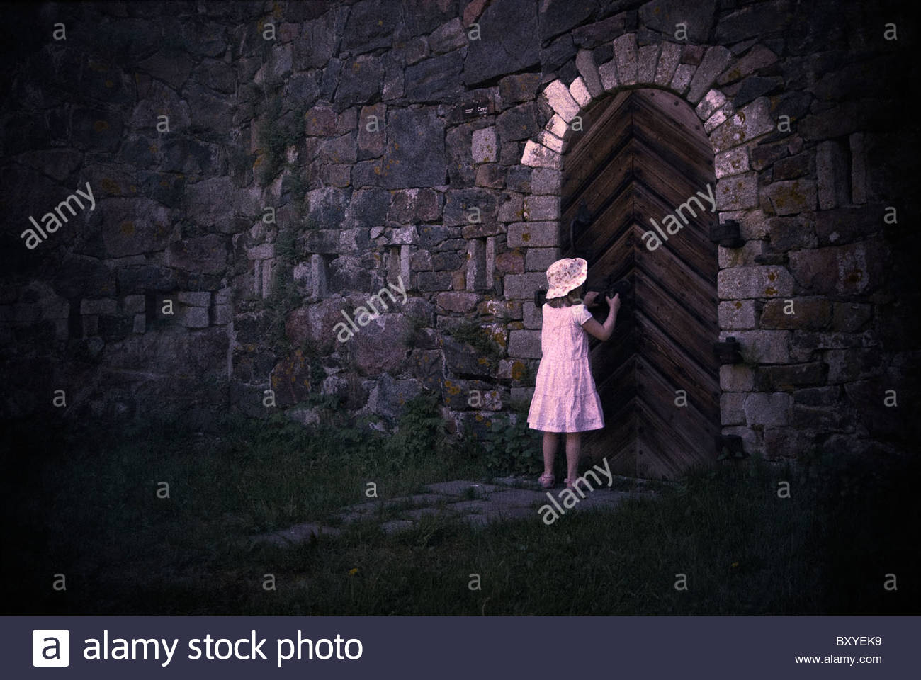 Young girl wearing a summer dress and hat opening a large wooden door in an old building - Stock Image