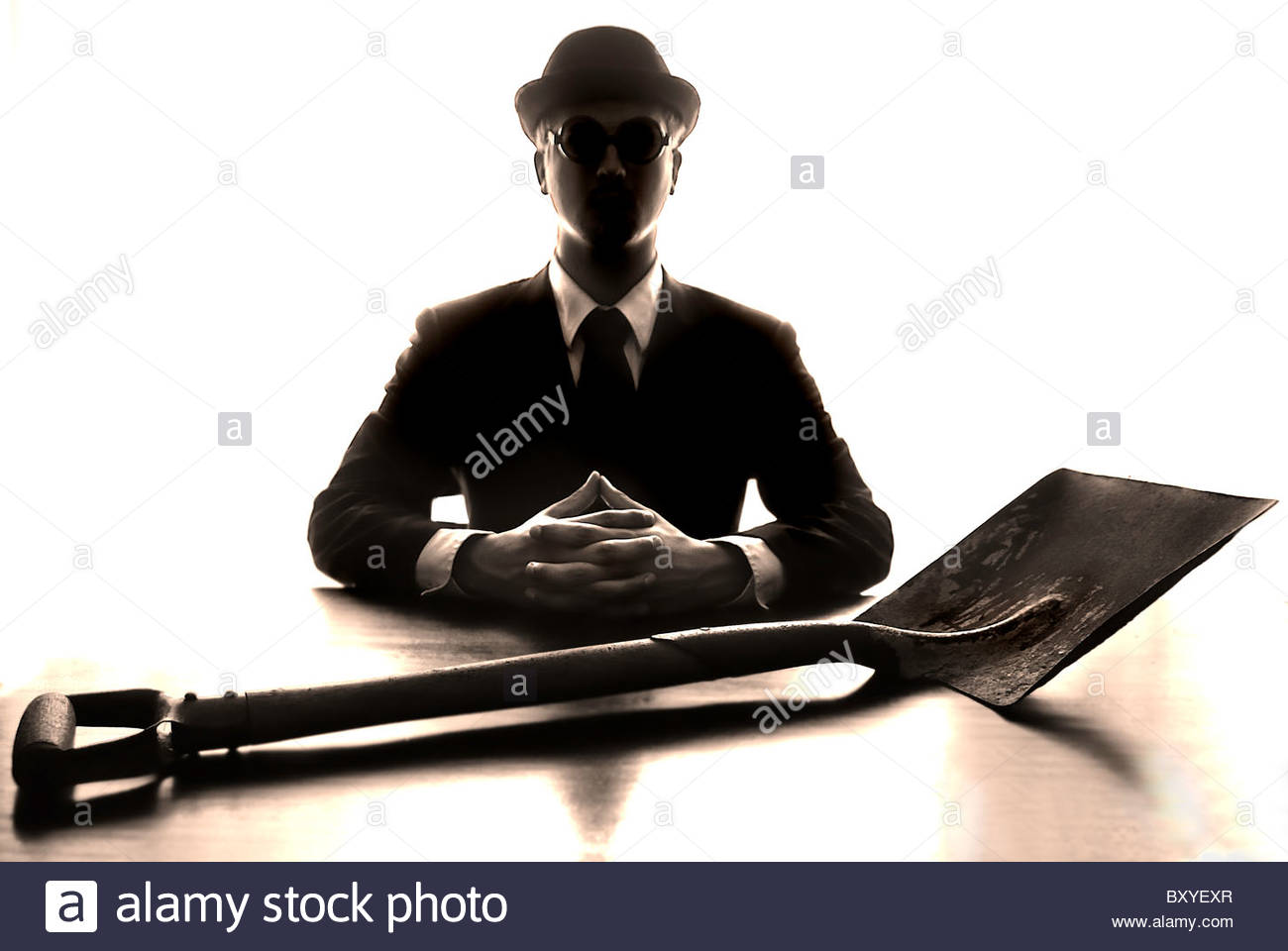Silhouette of male figure wearing a business suit and hat sitting behind desk with spade - Stock Image