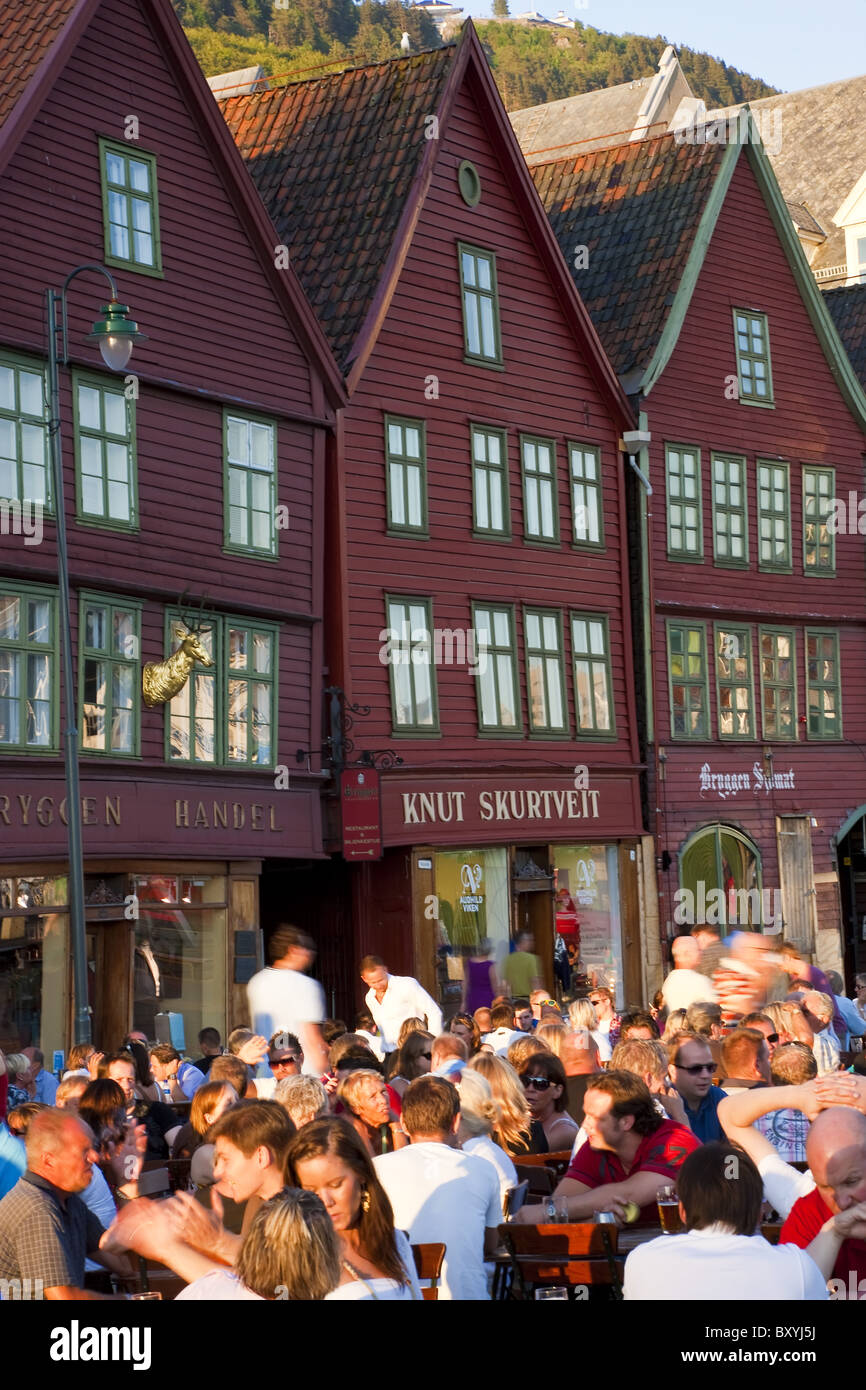People sat at pavement bars/cafes, Bryggen, the medieval quarter of Bergen, Hordaland, Norway - Stock Image