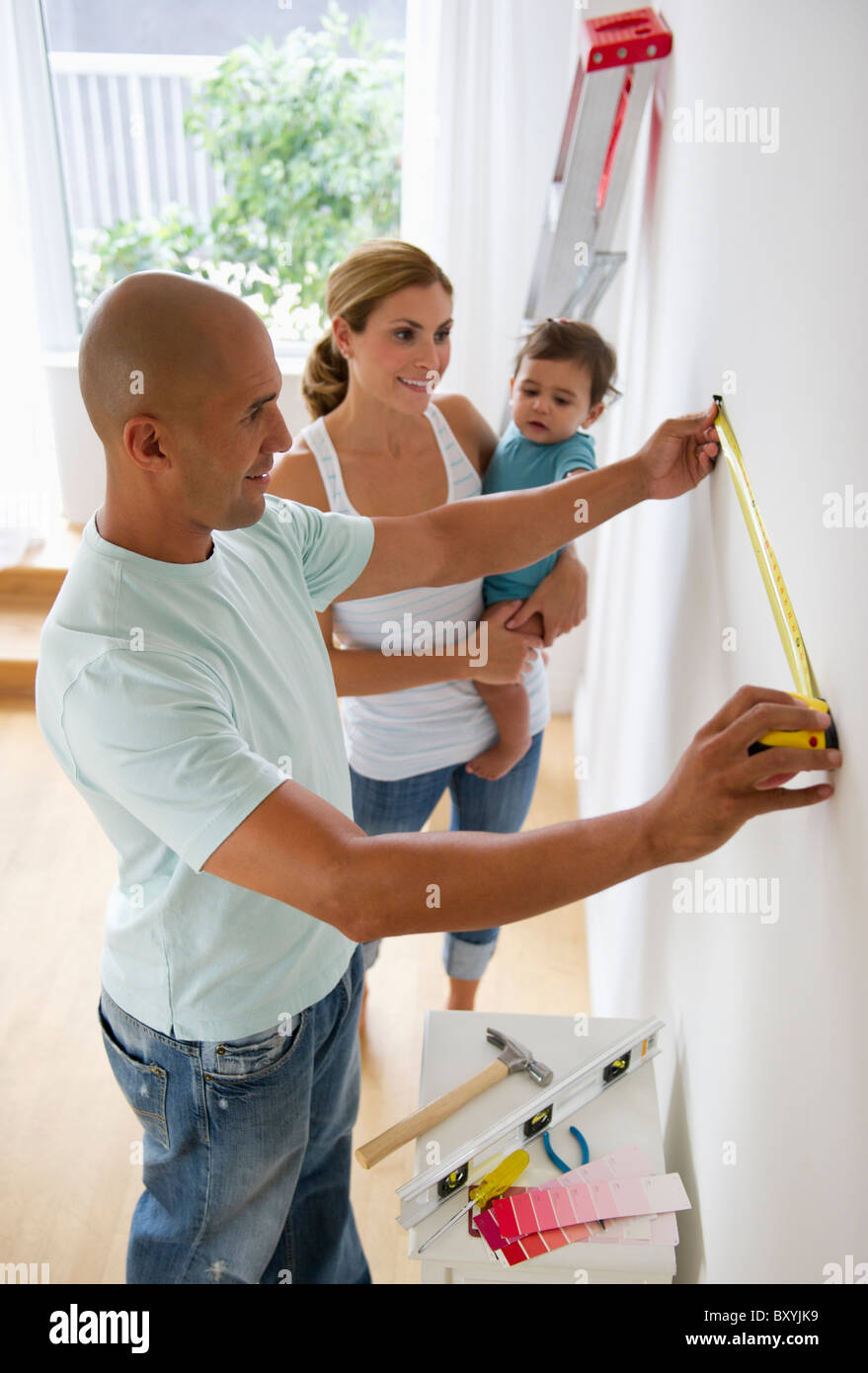 Young family with small girl refurbishing room - Stock Image