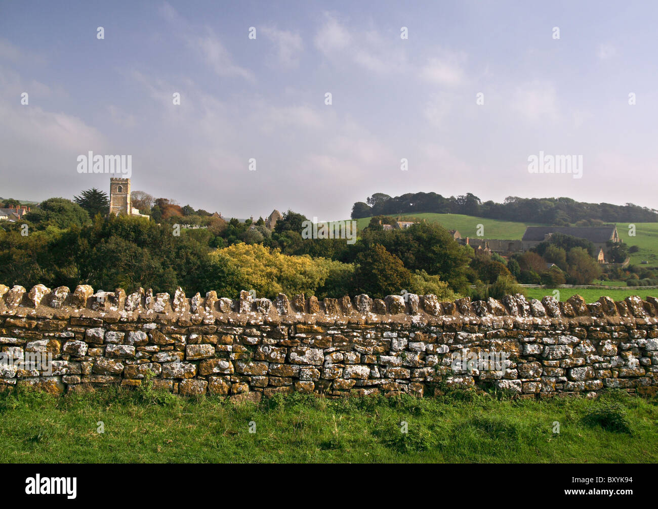 Typical English countryside scene, with an old stone wall, colorful trees and an old rural abbey - Stock Image