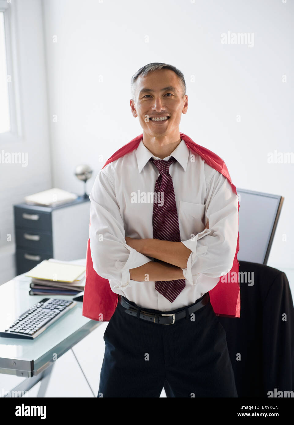 Portrait of smiling businessman wearing red cape - Stock Image