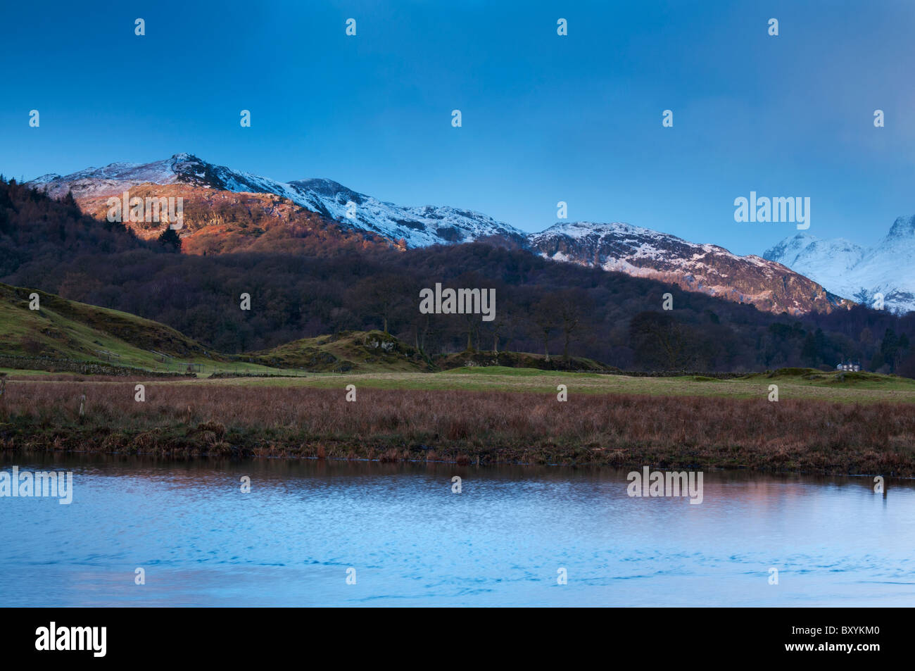 The rising sun lights up the snow topped fells at Elterwater in the Great Langdale Valley, Lake district Stock Photo
