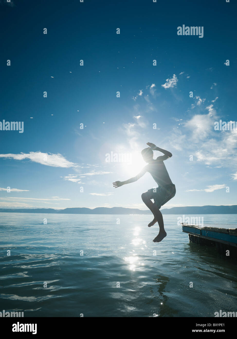 Boy jumping from raft - Stock Image