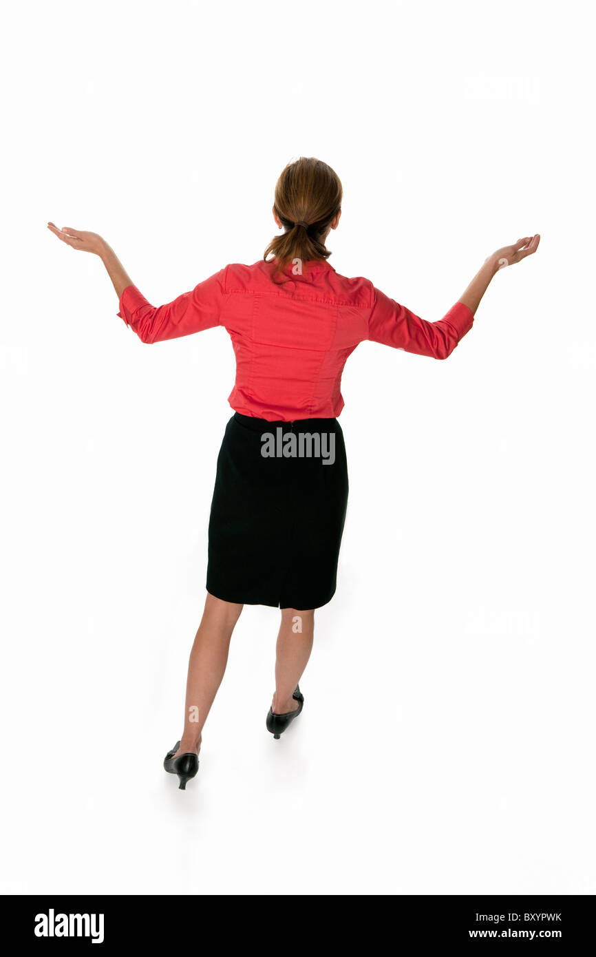 Backview of a business woman with arms raised - Stock Image