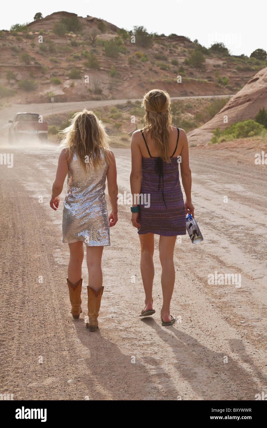 Two young women walking on dirt track in desert - Stock Image