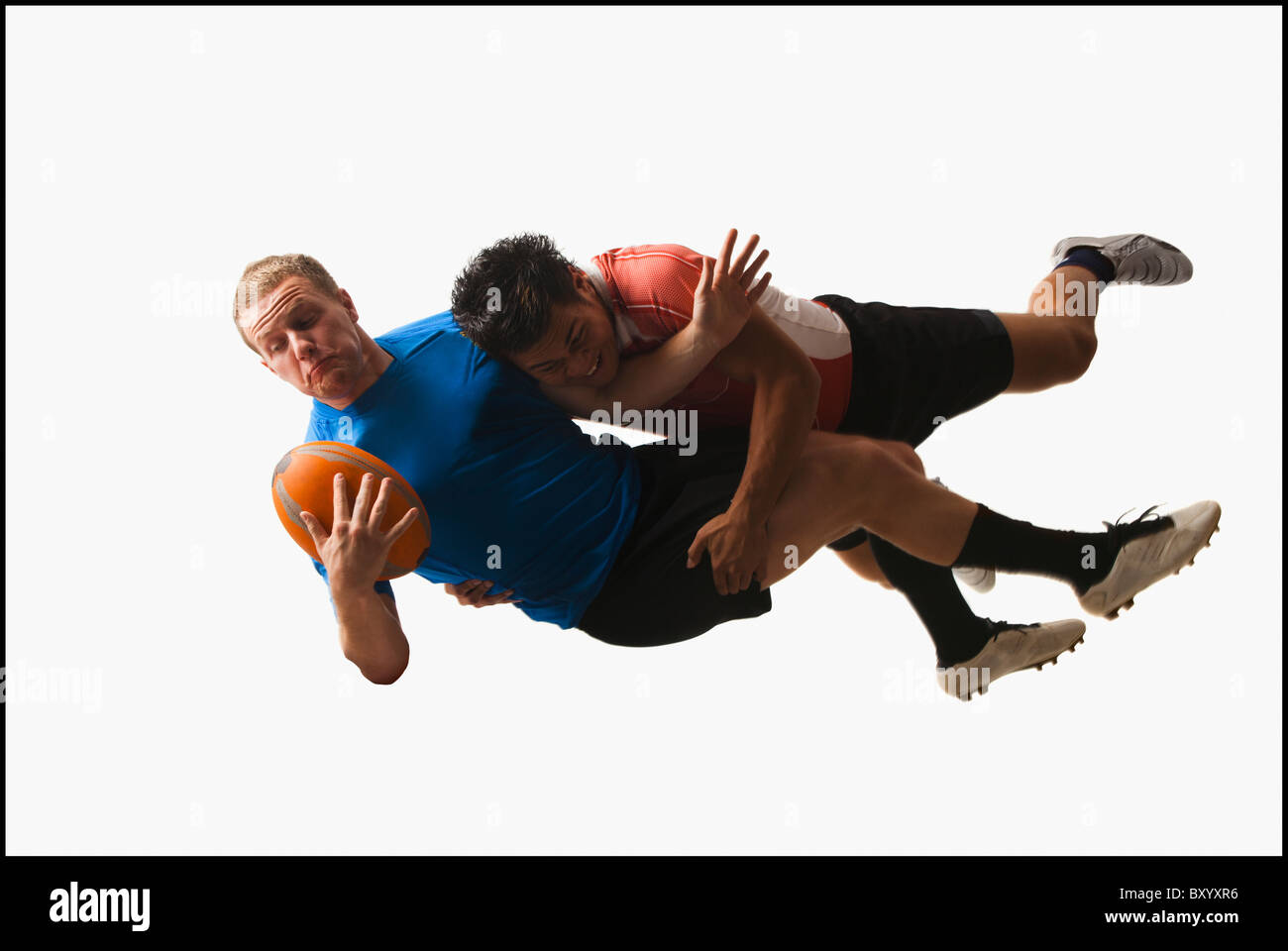 Rugby players tackling for ball - Stock Image