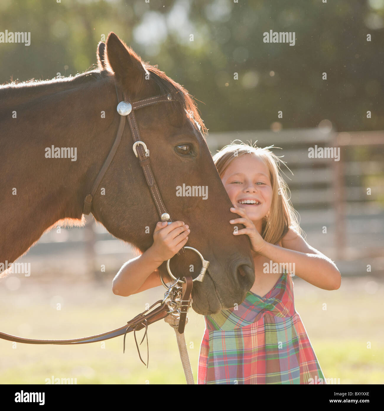 Portrait of smiling cowgirl with horse in ranch - Stock Image