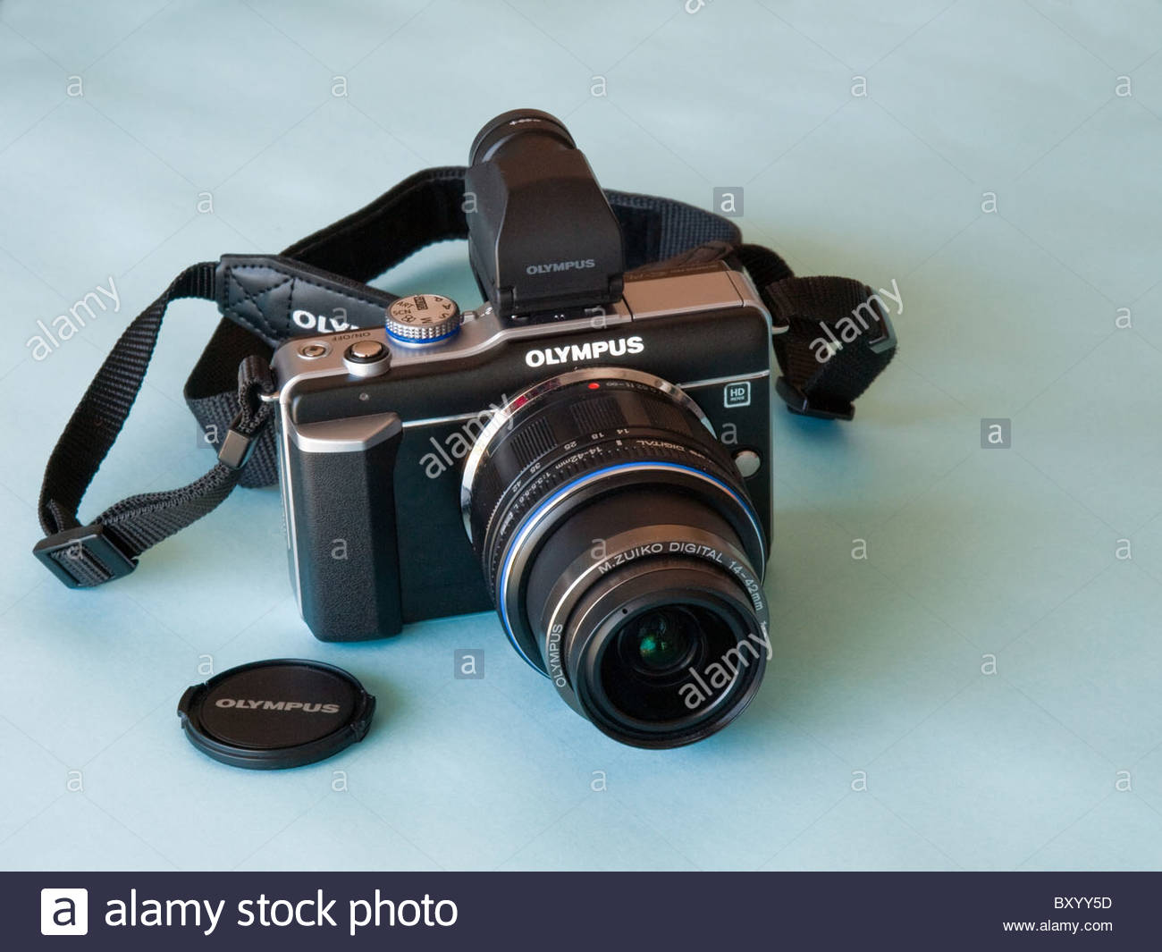 Olympus E-PL1 Compact digital -SLR  with a optional electronic viewfinder, strap and 14-42 kit lens on a pale blue - Stock Image