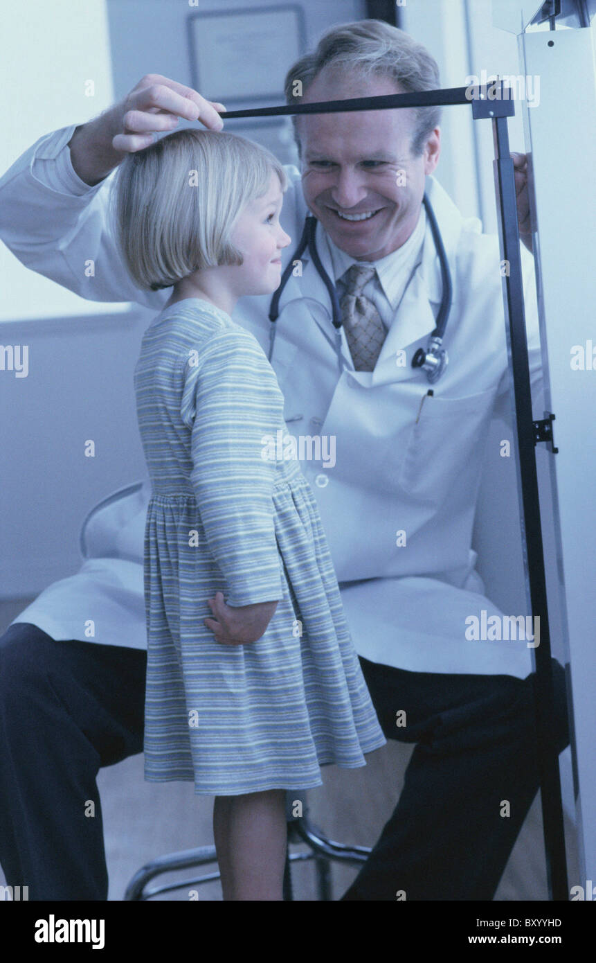 Doctor measuring young girl's growth - Stock Image