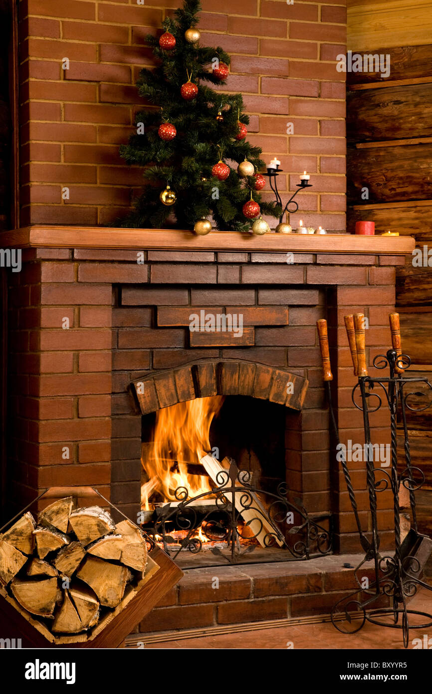 Image of chimney with fire inside and decorated tree on its top - Stock Image