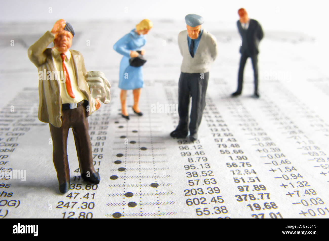 Business figurines on financial figures - Stock Image