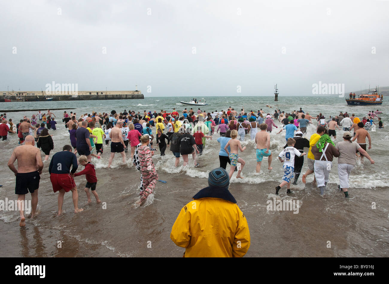 Hundreds of people run into the sea for annual new years day dip at Peel, Isle of Man Stock Photo