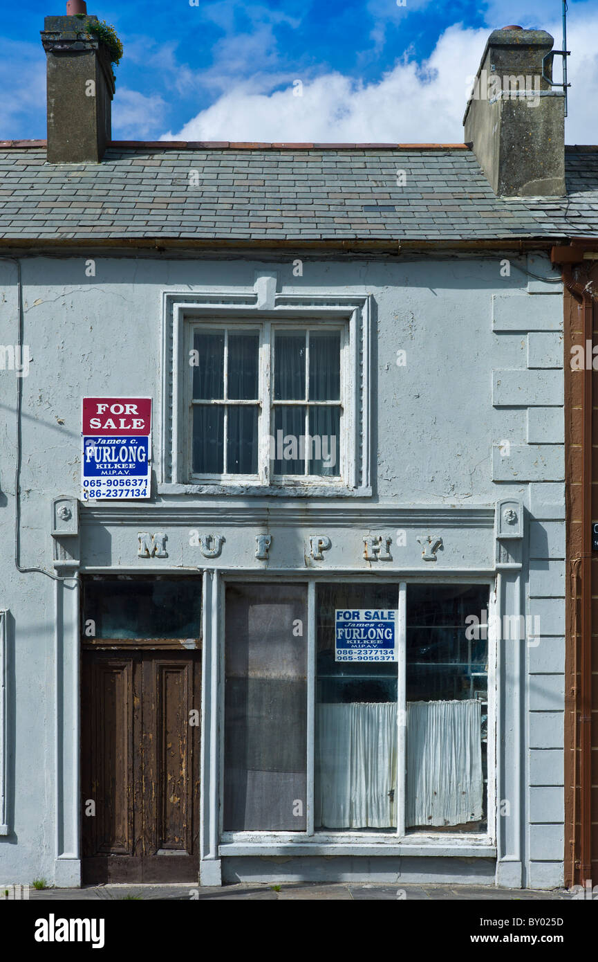 Rundown Murphy shop with estate agent for sale boards in, Kilkee, County Clare, West of Ireland - Stock Image