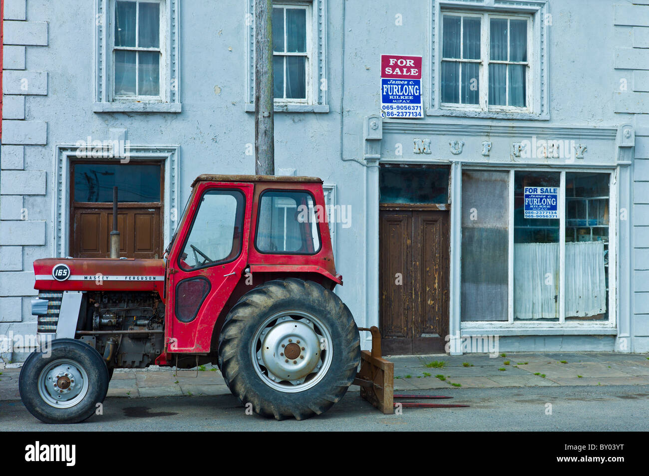Tractor parked at Murphy shop with estate agent For Sale boards in, Kilkee, County Clare, West of Ireland - Stock Image