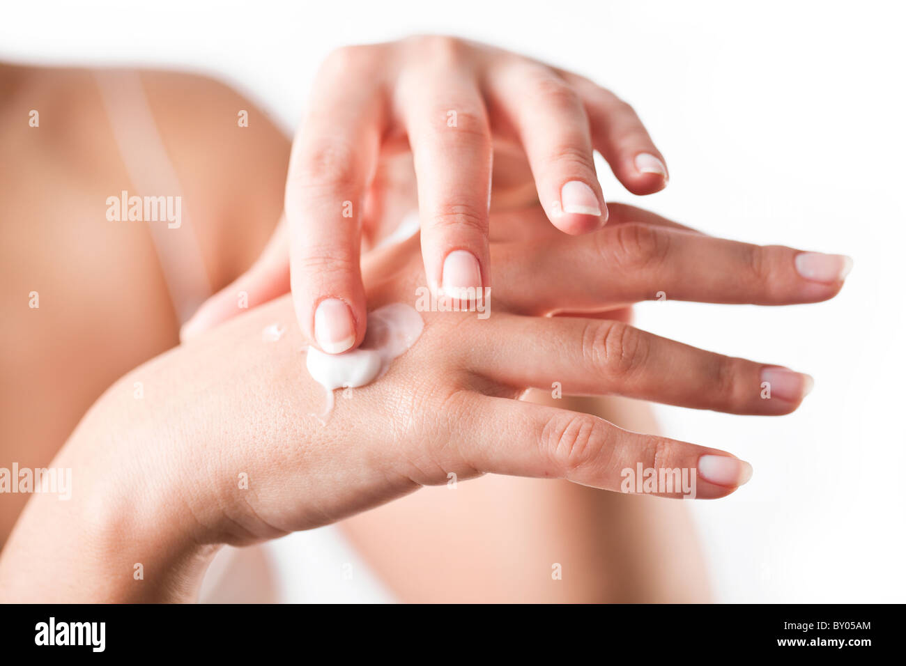 Smiling young woman applies cream on her hands. On a white background. - Stock Image